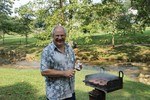 Grill master Carl Bailey with his weapon of choice at the 2012 picnic.